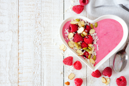 Healthy raspberry smoothie in a heart shaped bowl with almonds, pumpkin and chia seeds, coconut on a white wood background