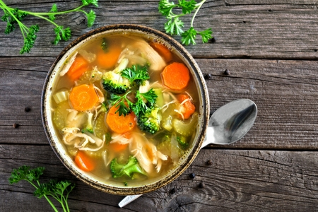 Homemade chicken vegetable soup, top view on an aged rustic wood background Stock Photo