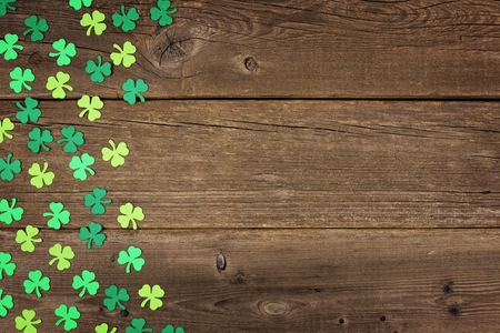 St Patricks Day side border of paper shamrocks over an old rustic wood background