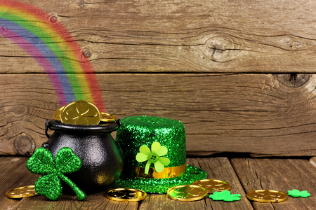 St Patricks Day Pot of Gold with rainbow, shamrocks and hat against rustic wood