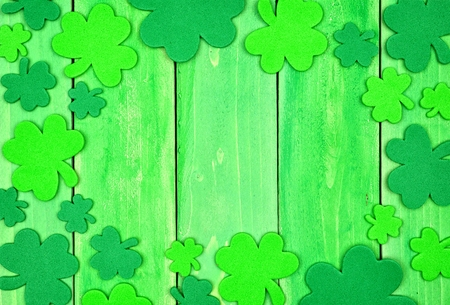 St Patricks Day frame of shamrocks over a green wood background Stock Photo