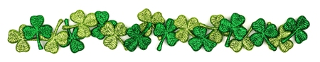 Long border of St Patricks Day shiny shamrocks over a white background Stock Photo