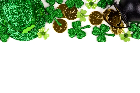 St Patricks Day top border isolated on a white background. Above view with Pot of Gold, shamrocks and leprechaun hat. Stock Photo