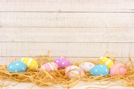 Easter Eggs in straw against an aged white wood background