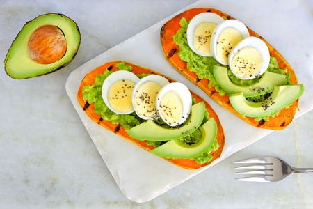 Sweet potato toasts with avocado, eggs and chia seeds on a marble server. Top view on a bright background. Stock Photo