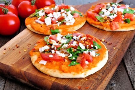 Spicy hummus mini flat breads with tomatoes and feta. Close up on paddle board with a wood background. Healthy eating concept.