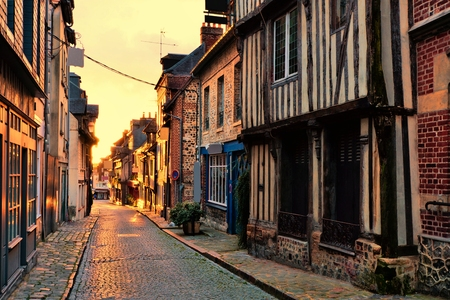 Old street in the Normandy town of Honfleur, France with light of the rising sun
