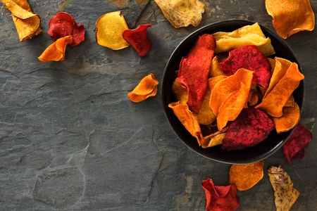 Bowl of mixed healthy vegetable chips. Top view, corner orientation with copy space on a dark stone background. Stockfoto