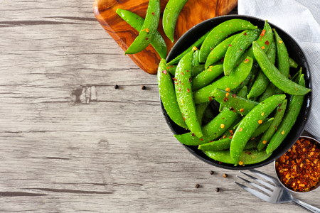 Bowl of healthy roasted snap peas. Top view, corner orientation with copy space on a wood background. Stock Photo