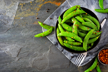 Bowl of healthy roasted snap peas. Top view, corner orientation with copy space on a dark stone background. Stok Fotoğraf