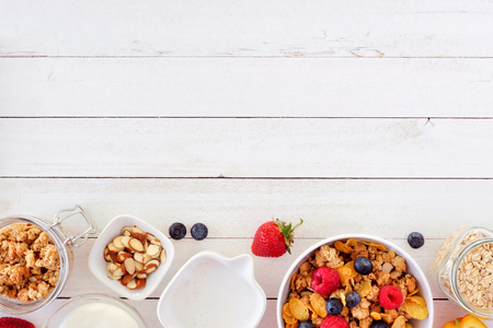 Cereal and ingredients for a healthy breakfast forming a bottom border over a white wood background. Top view. Copy space.
