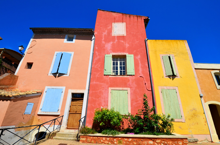 Vibrant houses in the old town of Rousillon, Provence, France with red and yellow ocher colors