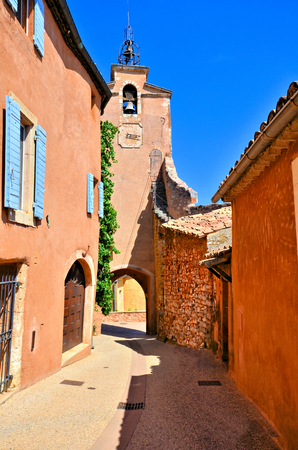 Vibrant street and bell tower in the old town of Rousillon, Provence, France with red colors Stock Photo