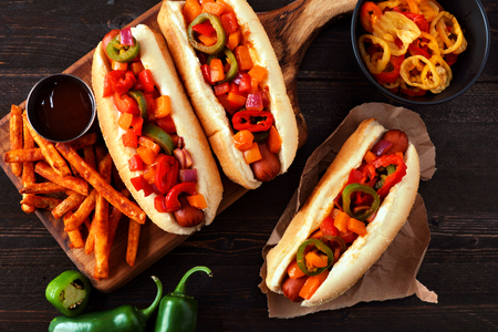 Hot dogs with spicy peppers, onions in BBQ sauce and fries. Top view scene on a dark wood background.