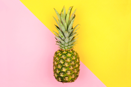 Pineapple on a modern pastel pink and yellow angular background. Minimal summer concept.