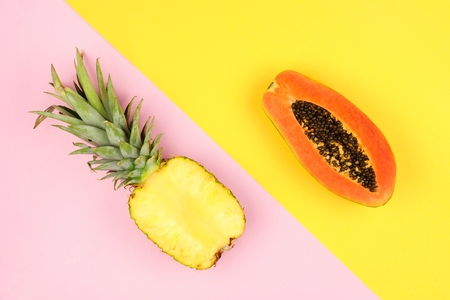 Half cut juicy pineapple and mango on a pastel pink and yellow background. Minimal summer concept. Angular orientation. 免版税图像