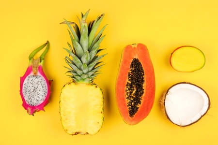 Tropical fruit flat lay with cut pineapple, dragon fruit, papaya, mango, and coconut on a bright yellow background