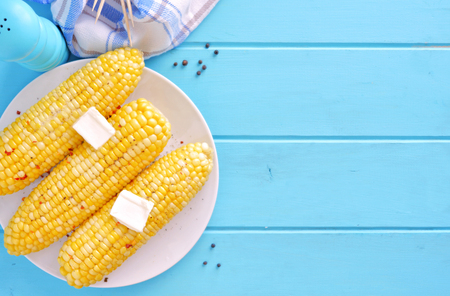 Summer corn on the cob. Top view scene, side orientation on a blue wood background. Stockfoto