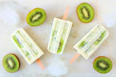 Kiwi vanilla yogurt ice cream pop on a bright marble background. Top view scene.