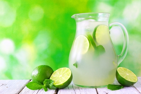 Jug of summer limeade on white wood against a green outdoor background Stock Photo