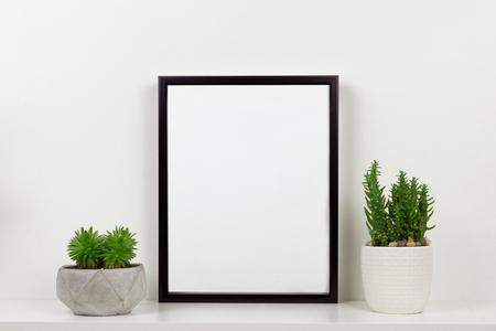 Mock up black frame and succulent plants in pot on a shelf or desk. White shelf and wall. Portrait frame orientation.