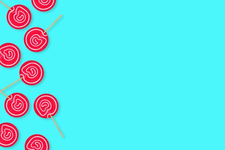 Side border of vibrant pink lollipops against a pastel blue background. Copy space. Stock Photo