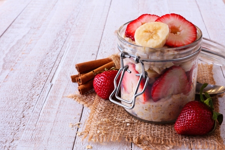 Overnight oatmeal with fresh strawberries and bananas in a jar on a white wood background