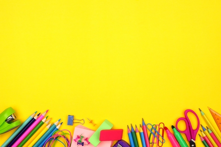 School supplies bottom border against a bright yellow paper background
