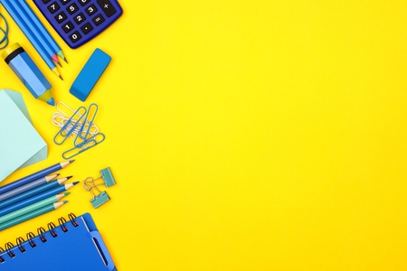 Blue school supplies side border against a bright yellow paper background Stock Photo