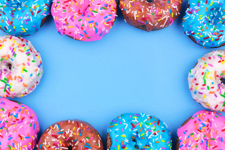 Frame of assorted donuts with frosting and sprinkles against a pastel blue background