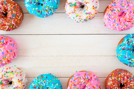 Frame of assorted donuts with pastel colored icing and sprinkles against a white wood background
