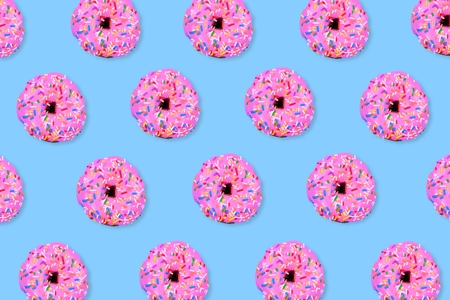 Colorful food pattern. Soft pink iced donuts on a pastel blue background. Top view.