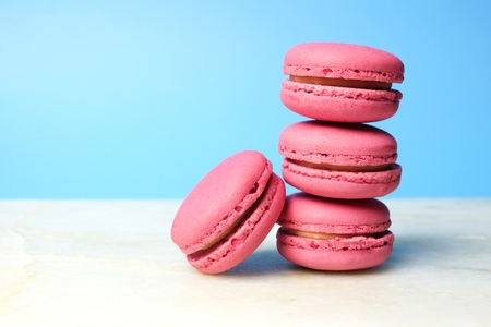 Stack of pink macaroons on a white and soft blue background Stock Photo