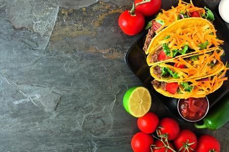 Hartschalentacos mit Rinderhackfleisch, Salat, Tomaten und Käse. Draufsicht, Eckrand auf einem dunklen Hintergrund mit Kopierraum. Standard-Bild