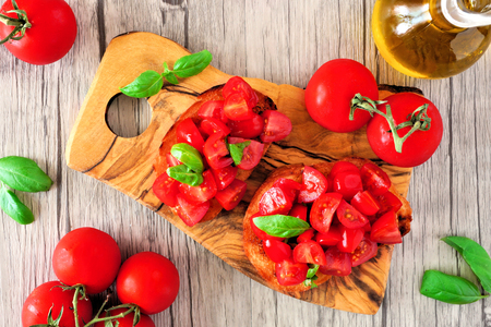 Bruschetta appetizers with cherry tomatoes and basil. Top view, close up with serving board over a wood background.