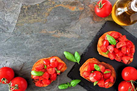 Bruschetta appetizers with cherry tomatoes and basil. Top view, corner border against a dark background. Copy space. Stock Photo