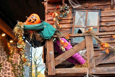 Halloween scarecrow with Jack o Lantern head. Autumn scene at a spooky house. Imagens