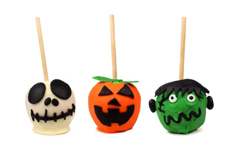 Three Halloween candy apples isolated on a white background. Skeleton, jack o lantern and monster.