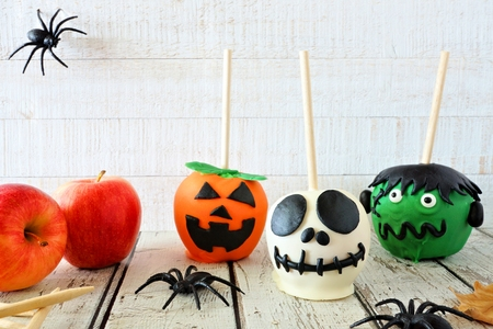 Halloween candy apple scene against a white wood background. Jack o lantern, skeleton and monster.