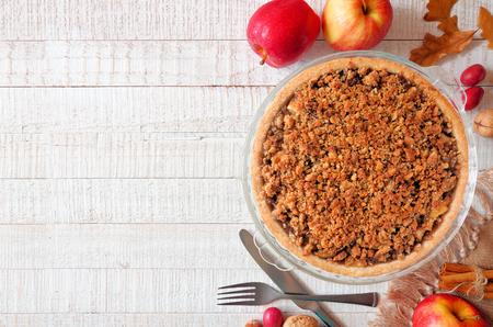 Apple Crumble Pie, Seitenansicht der Draufsicht auf einem weißen Holzhintergrund. Hausgemachtes Herbstdessert. Speicherplatz kopieren.