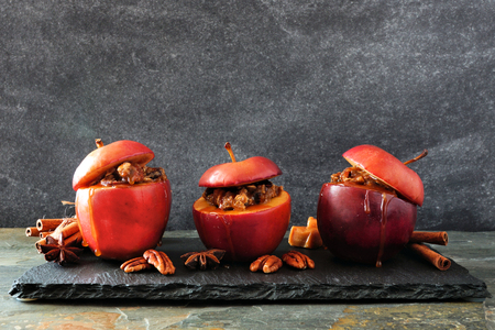 Baked apples with caramel, brown sugar and and nuts. Serving platter on a dark background. Homemade autumn dessert. Stock Photo