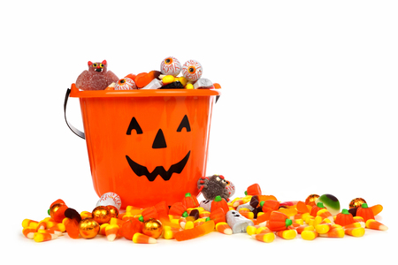 Halloween Jack o Lantern candy collector with a pile of candy over a white background