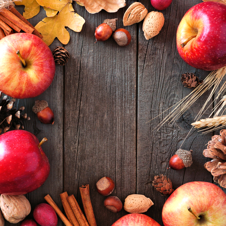 Autumn square frame of apples and fall ingredients on a rustic wood background with copy space