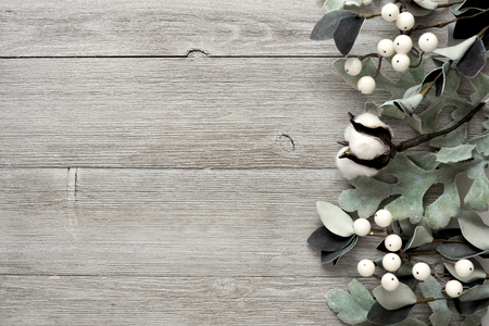 Side border of silver green leaves and white berries over a rustic gray wood background. Top view with copy space.