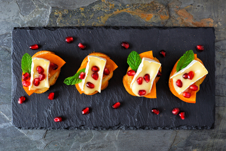 Holiday crostini appetizers with persimmons, pomegranates and brie cheese. Overhead view, on a slate server.