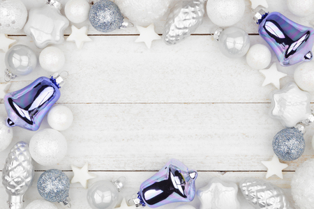 Christmas frame of blue and white decorations, top view over a rustic white wood background