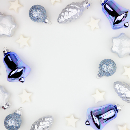 Christmas square frame of blue and white decorations, top view over white background