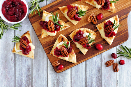 Holiday flatbread appetizers with cranberries, pecans and brie cheese. Top view table scene on a wooden platter. Reklamní fotografie