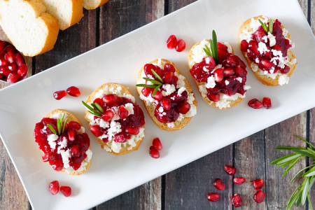 Holiday crostini appetizers with cranberries, pomegranates and feta cheese. Above view on a serving plate over a wood background.