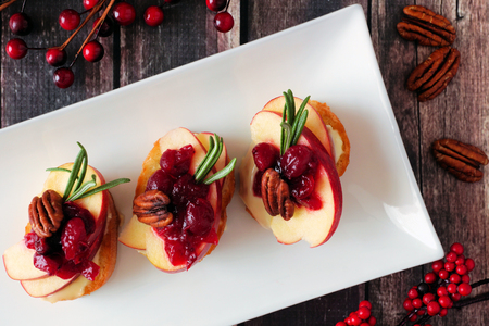 Crostini appetizers with apples, cranberries, brie and pecans. Above view, close up on a serving plate over a wood background. Stok Fotoğraf